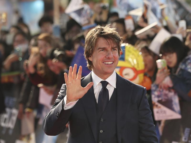 Actor Tom Cruise waves to fans as he attends a red carpet event to promote his latest movie Jack Reacher: Never Go Back in Seoul. (AP)