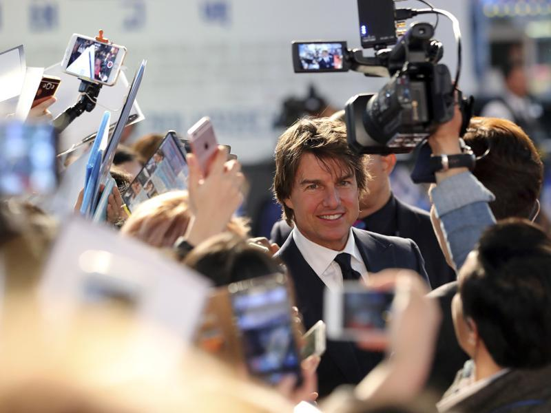 Actor Tom Cruise is surrounded by fans and photographers as he arrives for a red carpet event to promote his latest movie Jack Reacher: Never Go Back in Seoul. (AP)