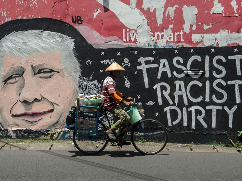 Republican Presidential nominee Donald Trump has been openly criticised for tweeting quite liberally and, often, offensively. Here a man cycles past graffiti condemning Donald Trump, on a street in Surabaya, Indonesia's east Java on October 17, 2016. (AFP Photo)
