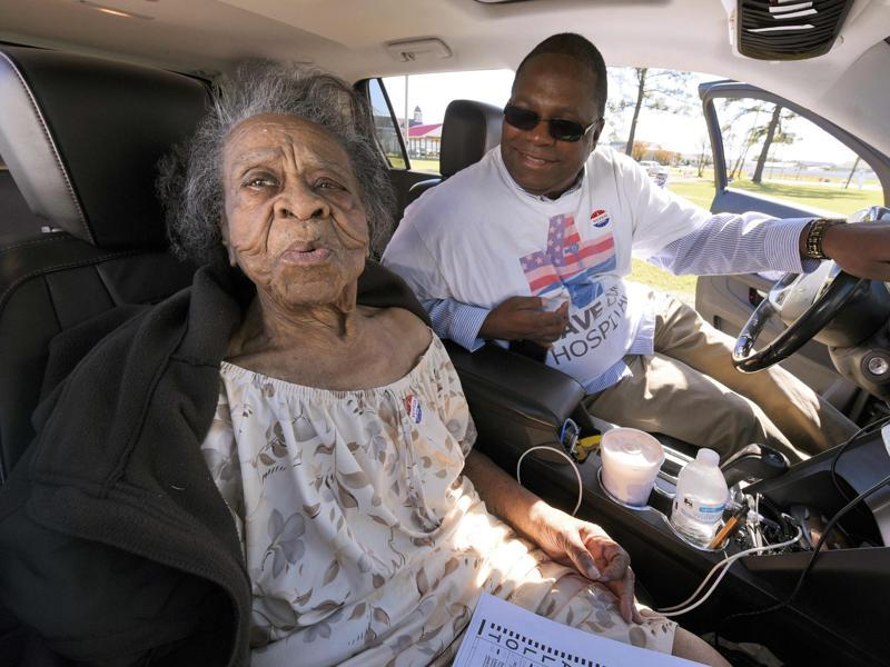Grace Bell Hardison, a 100-year-old woman recently mentioned by President Barack Obama after attempts were made to purge her from the voter registration list and hence deny her right to vote, reacts after a kiss from her nephew Greg Satterthwaite after she voted in the U.S. general election from his car in Belhaven, North Carolina. (REUTERS)