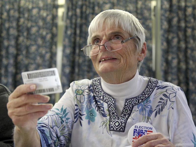 Ballot clerk Patricia Timbury checks a voter's identification during the U.S. presidential election in Woodstock, New Hampshire. (REUTERS)