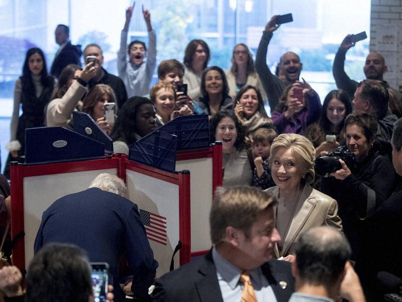 Democratic presidential candidate Hillary Clinton, accompanied by her husband, former President Bill Clinton, left, smiles as she votes at Douglas G. Grafflin School in Chappaqua, New York, on November 8. At far left is senior aide Huma Abedin.  (AP)