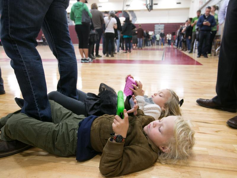 Merrick, 4, (front) and Savannah Little, 5, entertain themselves with electronic devices while waiting in line with their parents on election day November 8, 2016 at Grady High School in Atlanta, Georgia. After a contentious campaign season, Americans go to the polls today to choose the next president of the United States.  (AFP)