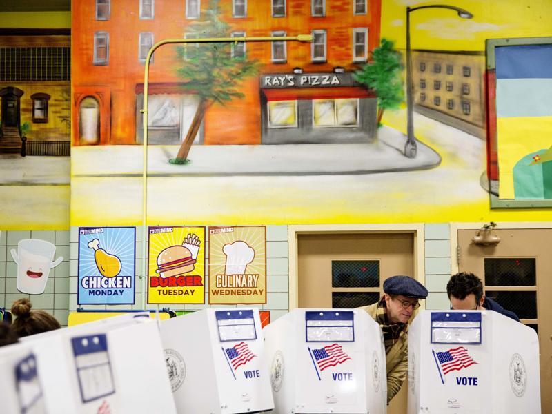 Peter McGough, left, talks with Adam Scheffer as they vote in a school cafeteria in New York.