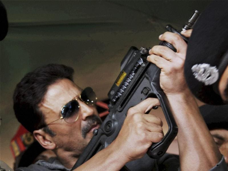 Akshay Kumar inspects a firearm during a visit to BSF's Paloura camp in Jammu. (PTI Photo)