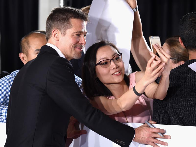 Actor Brad Pitt gets a selfie taken with a fan at the premiere of Paramount Pictures' Allied. (AFP)