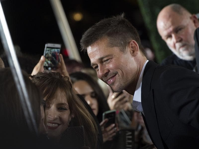 Actor Brad Pitt clicks pictures with his fans at a screening of his new World War II thriller Allied. (AFP)