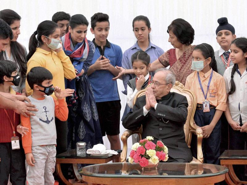 President Pranab Mukherjee meeting the students and teachers on the occasion of Children's Day at the Rashtrapati Bhavan in New Delhi on Monday. (PTI)