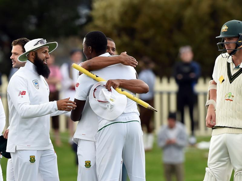 South Africa's players Hashim Amla (L), Vernon Philander (2nd L) and Kagiso Rabada celebrate their victory as Australia's batsman Josh Hazlewood (R) looks on. (AFP photo)