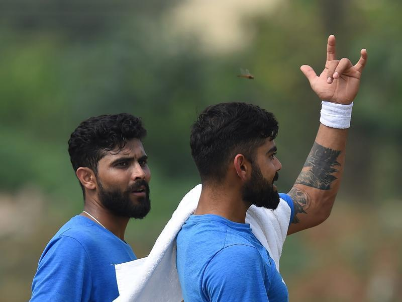 India's captain Virat Kohli (R) gestures while giving bowling tips to Ravindra Jadeja on Wednesday. Jadeja went wicketless in England's second innings in Rajkot. (AFP)