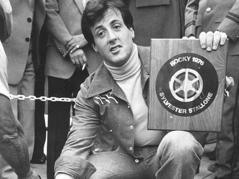 In this September 22, 1977 photo, actor and screenwriter Sylvester Stallone poses with a terrazzo inlay to be placed in the streets of the Westwood section of Los Angeles. He had become a big star after Rocky, which was released on November 21, 1976. (AP Photo)