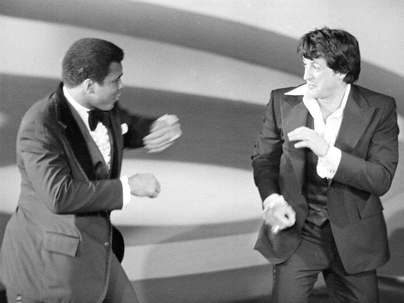 Muhammad Ali makes a surprise appearance on the Academy Awards show, playfully sparring with actor and screenwriter Sylvester Stallone in Los Angeles in March, 1977. (AP Photo)