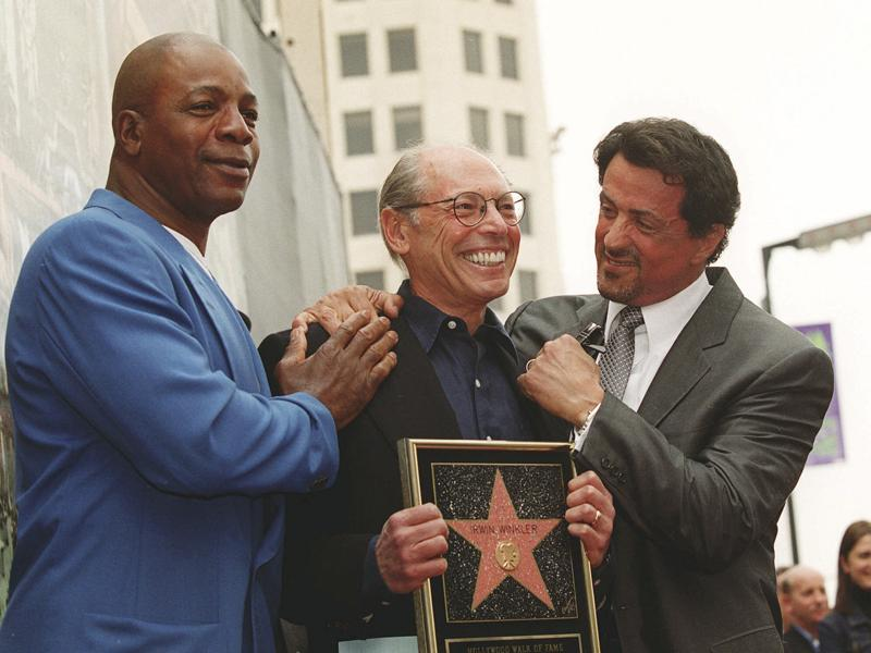 Sylvester Stallone and his Rocky co-star Carl Weathers pose with producer Irwin Winkler at the Walk of Fame ceremony for Winkler in the Hollywood section of Los Angeles. (AP Photo)