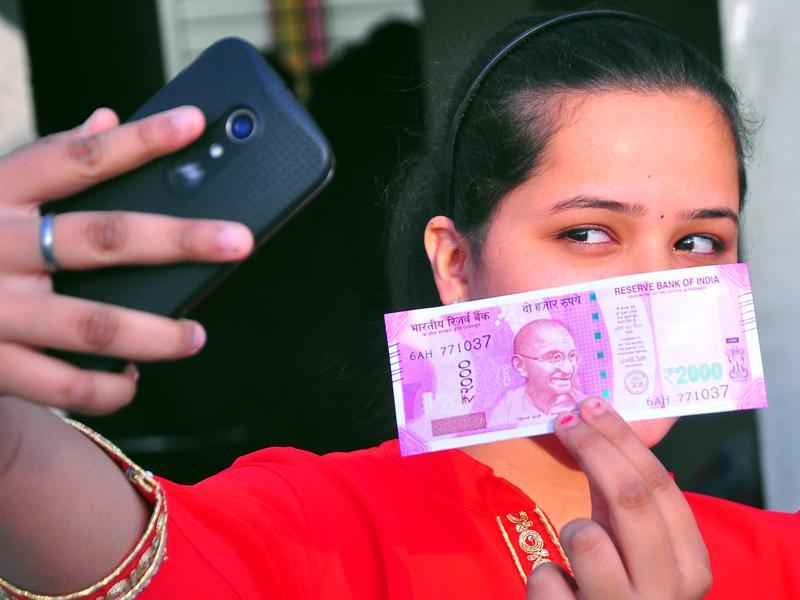 No selfie crunch: A woman strikes a new pose with a new Rs2,000 note. (mayur bargaje/ht photo)