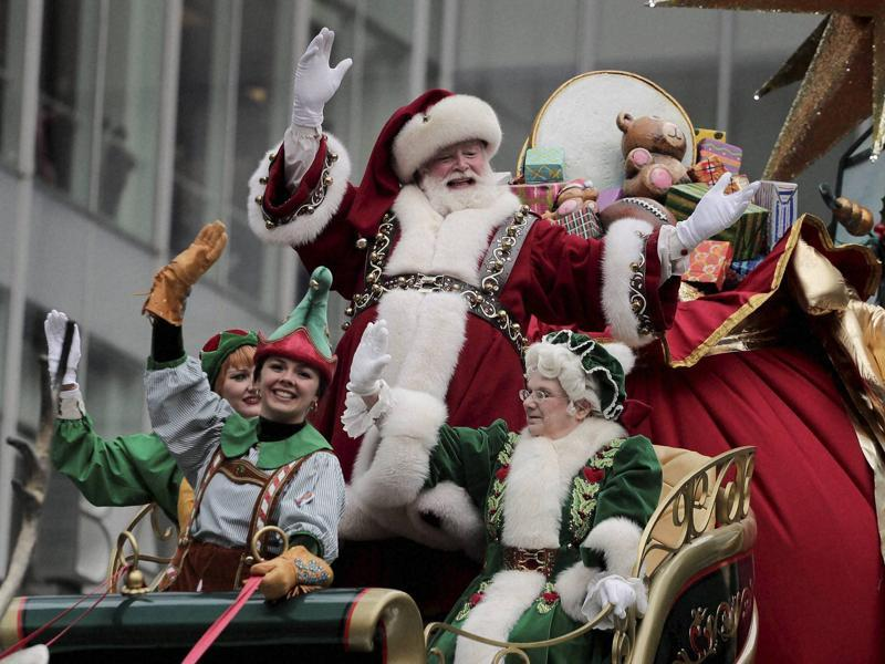 Santa Claus waves from his float as he passes by a street full of spectators.  (AP)