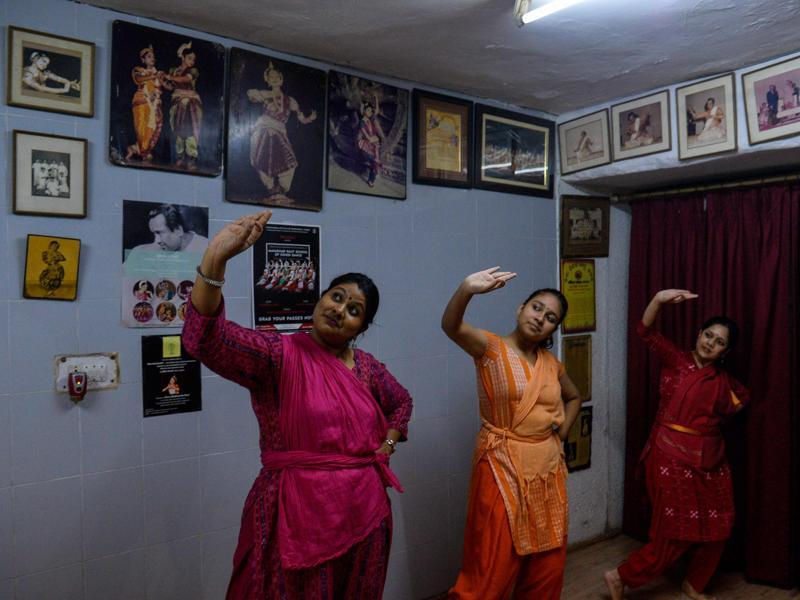 (L-R) Students Priyanka Venkateswaran (36), Ankita Nayak (16) and Rujuta Pandav (33) participate in an Odissi dance lesson in New Delhi.  Its basic dance motif is the bhangas (symmetric body bends, stance). (AFP)