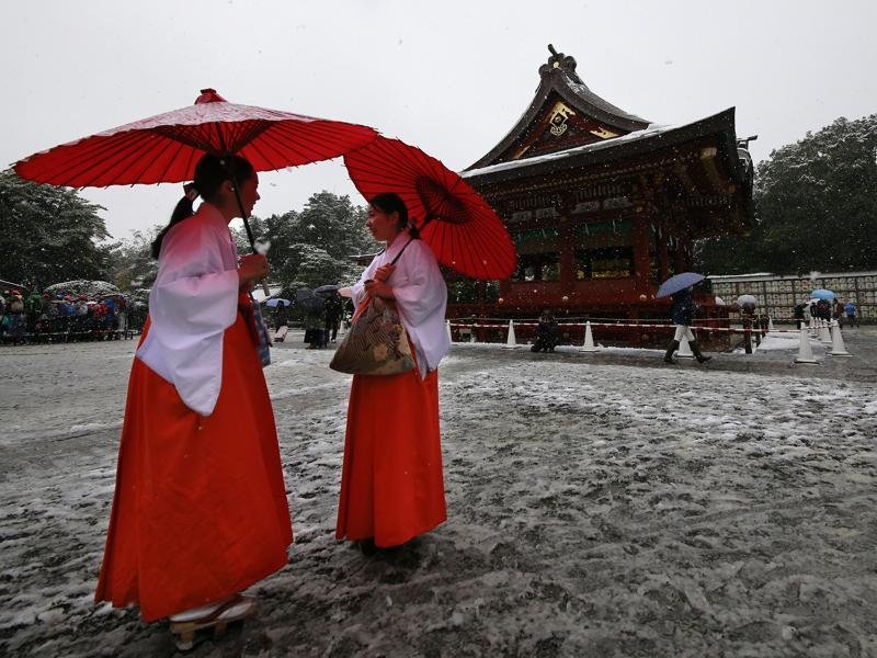 Shrine maidens chat in the snow at the Tsurugaoka Hachimangu Shrine in Kamakura, near Tokyo.(AP Photo/Shizuo Kambayashi) (AP Photo)