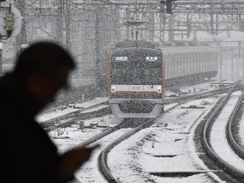 A train approaches a station in snowfall in Tokyo. (AFP Photo)