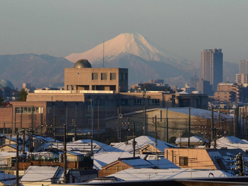 A snow-capped Mount Fuji is seen in the background as roofs of houses are covered with snow in Tokyo. (AFP Photo)
