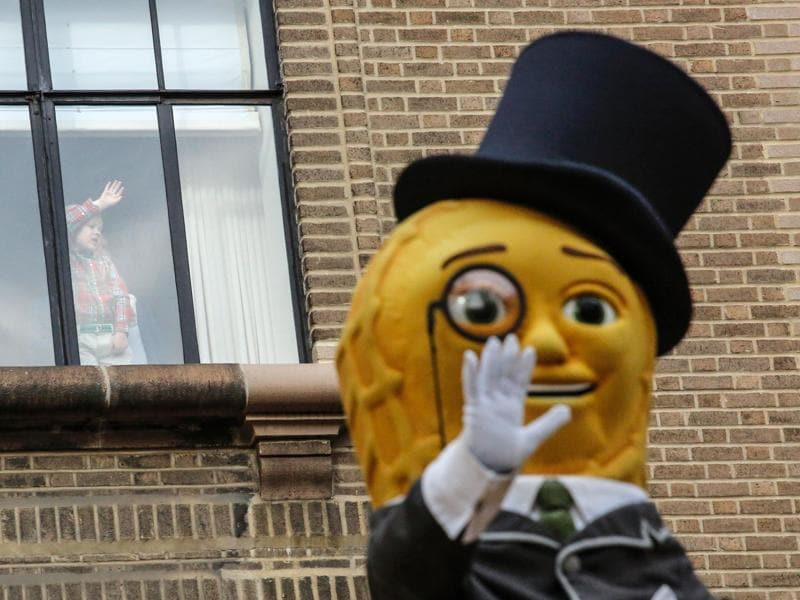 A child watches from her window as a Mr Peanut waves to the crowd. (AFP)