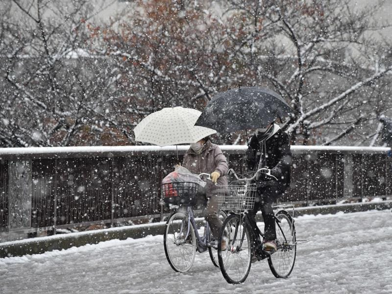 People cycle in snowfall in Tokyo. (AFP Photo)