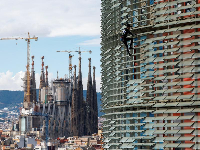 French climber Alain Robert, also known as 'The French Spiderman', scales the 38 storey skyscraper Torre Agbar in Barcelona on November 25, 2016. The 19th century Sagrada Familia cathedral, construction for which is yet to be completed, can be seen in the background. (Albert Gea/Reuters)