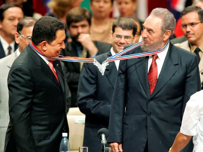 Venezuela's President Hugo Chavez (L) and his Cuban counterpart Fidel Castro joke after joining their medallions, given by medical graduates, at Havana's Karl Marx theatre, in this August 20, 2005 file photo. (REUTERS)