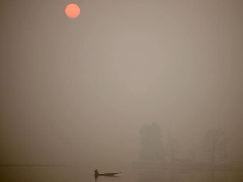 Fog shrouds Kashmir's Dal lake during sunset as a fisherman rows his boat in Srinagar on November 23, 2016. A cold wave is going through Jammu and Kashmir, with most places recording sub-zero temperatures.  (Tauseef Mustafa/AFP)