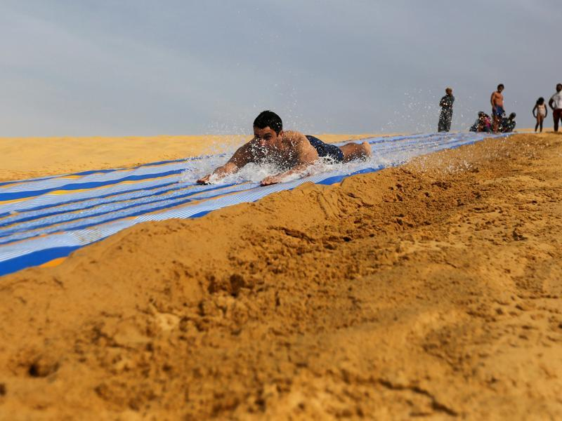 The place is also famous for its extensive mobile sand dunes. A man slides down a ramp leading up to the lake. (REUTERS)
