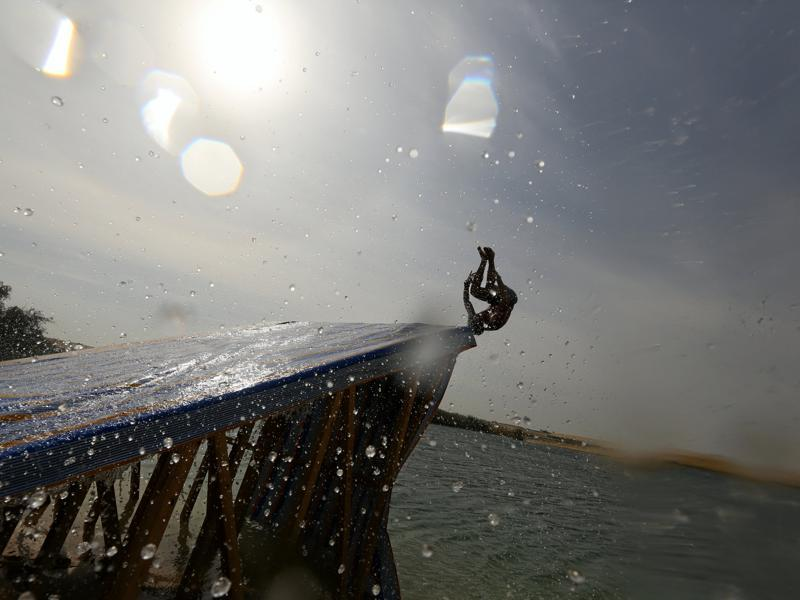 A man slides down a ramp into the lake. (REUTERS)