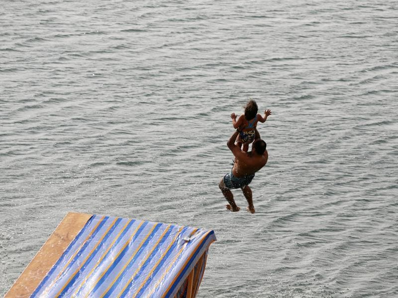 A man carrying his daughter slides down a ramp into the lake in Wadi el-Rayan Fayoum. (REUTERS)