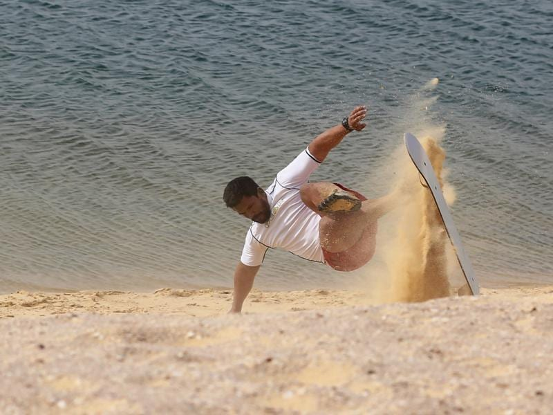 A man falls while sandboarding. (REUTERS)