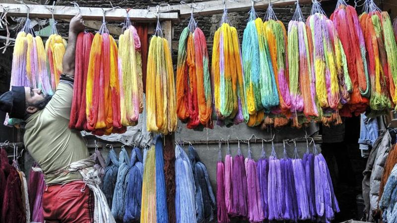 A Kashmiri man hangs dyed threads to dry at a dyeing centre in downtown Srinagar on December 26, 2016. Kashmiris have been dyeing fabric and threads manually for around two centuries and are known for their style of embroidery using these colourful threads. The practise though is on a decline as the manual labour is exhausting and takes a toll on workers. (Waseem Andrabi / Hindustan Times)
