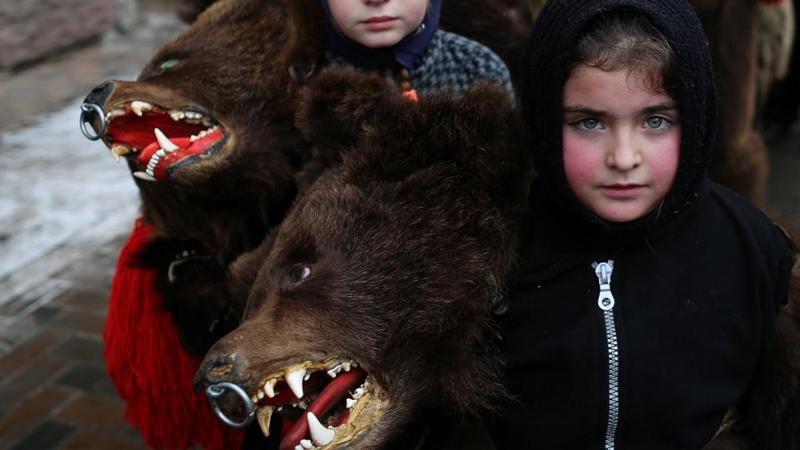 Children wearing costumes made of bearskins take part in a festival at Comanesti town in Romania on December 30, 2016. People from this region follow a pre-Christian rural tradition where they sing and dance in bear skin costumes to ward off evil. (Stoyan Nenov / REUTERS)