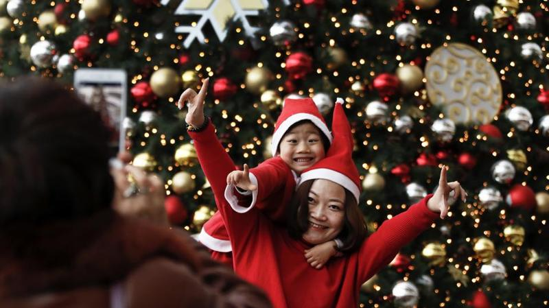 A mother and child, dressed in Santa Claus' hats, pose in front of a giant Christmas tree at a shopping mall in Beijing, on December 25, 2016. Although Christmas is not traditionally celebrated in China, shopping malls and retailers welcome the festival by organizing activities to attract shoppers as a chance to boost the year-end sales.  (Andy Wong / AP)