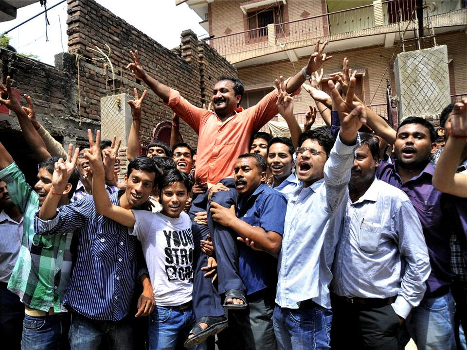 Founder of Super 30, Anand Kumar  (lifted up), with students celebrating their success in cracking the tough  exams for entrance to Indian engineering colleges
