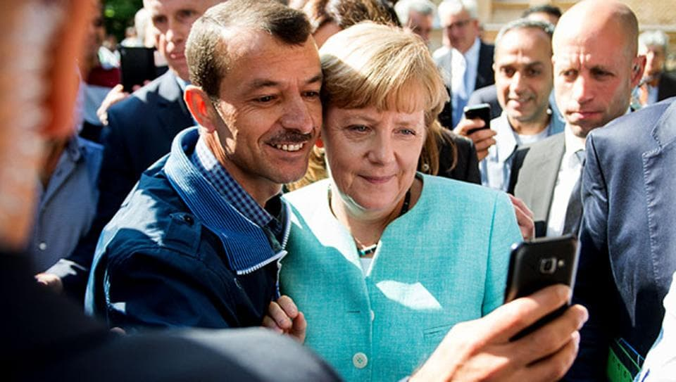 An asylum seeker takes a selfie with German Chancellor Angela Merkel following her visit to a branch of the Federal Office for Migration and Refugees and a camp for refugees in Berlin, 2017