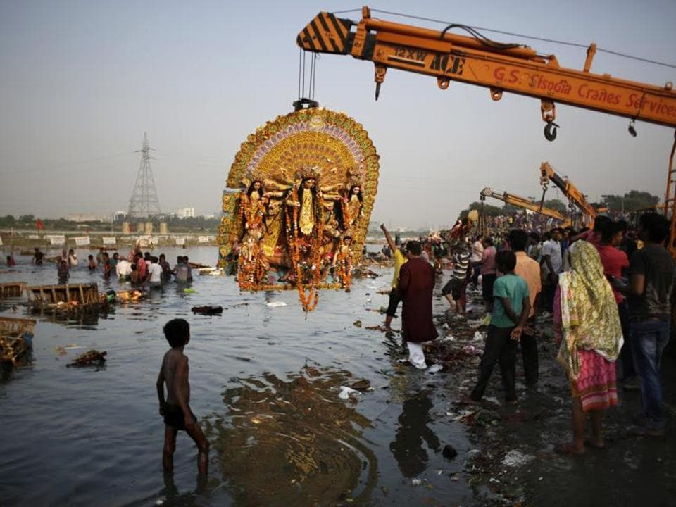 A giant Idol of Hindu goddess Durga suspends from a crane before it is immersed in the River Yamuna during Durga Puja festival in New Delhi.