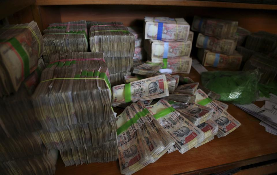 FILE - In this Nov. 10, 2016 file photo, discontinued Indian currency notes of 1,000 denomination are seen after they were deposited by people at a bank in Bangalore, India. Indian prime minister Narendra Modi, in his Nov. 8 televised address, announced the demonetization of India's 500 and 1,000-rupee notes, which made up 86 percent of the country's currency. There are doubts about whether the demonetization drive will truly make an impact on corruption and tax evasion. India's underground economy is so big it accounts for up to a quarter of the country's gross domestic product. And many of those possessing piles of black money have come up with ways to save much of it without drawing government attention. (AP Photo/Aijaz Rahi, File)