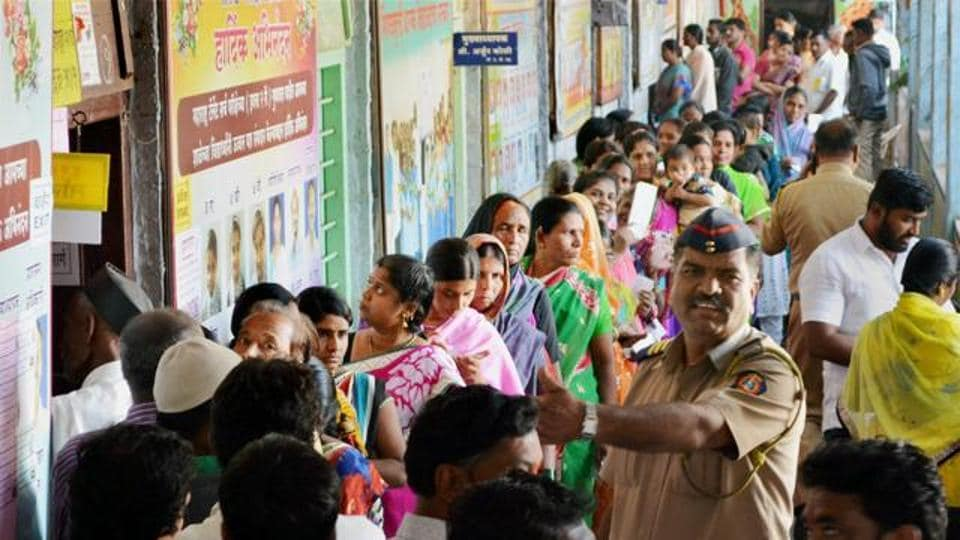 Voters stand in a queue to cast their votes at a polling booth for Municipal Council Elections in Karad, Maharashtra.