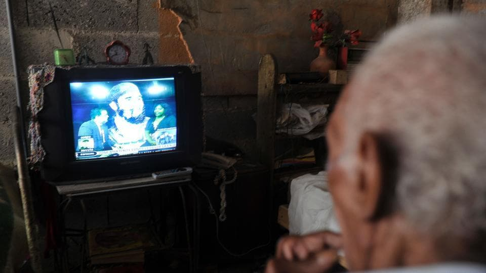A man watches on TV a program in homage to late Cuban revolutionary icon Fidel Castro in Havana, on November 28, 2016. Hundreds of thousands of Cubans swarmed Havana's iconic Revolution Square in a tearful and nostalgic tribute to Fidel Castro on Monday, kicking off a week-long farewell to the divisive Cold War icon.  (AFP)