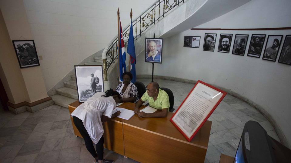 A woman signs a book of condolences, and a loyalty oath for the late Fidel Castro at the Journalists and Writers Union Federation building in Havana, Cuba, Monday, Nov. 28, 2016. Cubans on Monday began bidding farewell to Castro, the man who ruled the island for nearly half a century.  (AP)