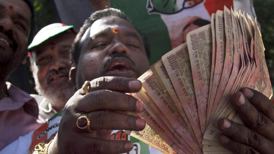 A person holds banned 500 and 1000 rupee notes during a protest against the government's decision to withdraw high denomination notes from circulation, in front of RBI in Hyderabad on Monday.