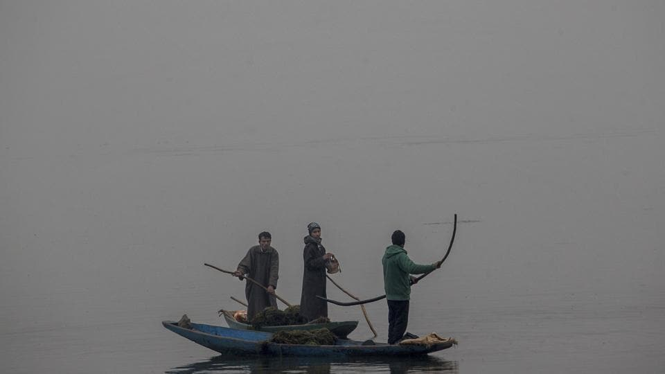 A Kashmiri worker warms his hands on a Kangri or traditional fire pot as he takes break from removing weed on a cold and foggy day at the Dal Lake in Srinagar. Cold conditions continued in most parts of Kashmir with fog affecting air traffic and normal life. (AP)