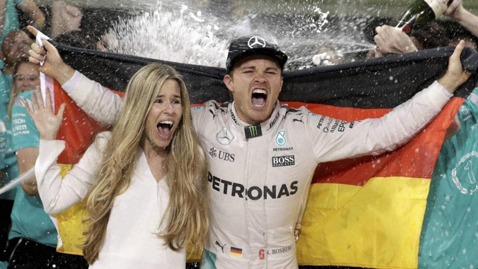 Mercedes driver Nico Rosberg of Germany celebrates with his wife Vivian Sibold holding a German flag in the team garage after winning the F1 2016 Championship in the Emirates Formula One Grand Prix at the Yas Marina racetrack in Abu Dhabi. (AP Photo)