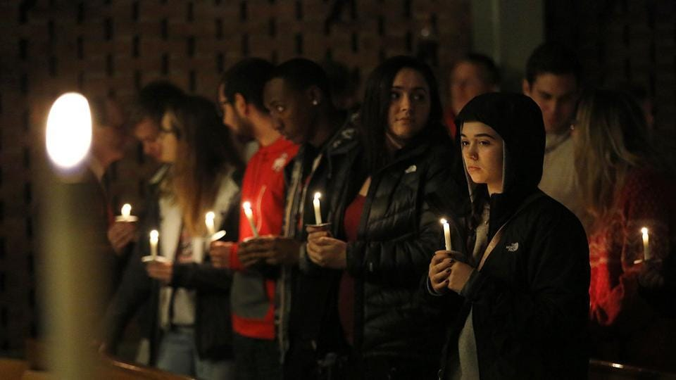 Guests stand for a moment after lighting their candles during a vigil at St Stephen's Episcopal Church in Columbus, Ohio.