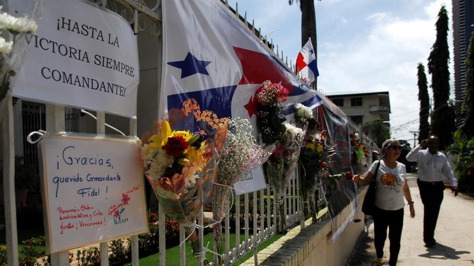 People walk past the fence of the Cuban embassy in Panama City where Fidel Castro's followers placed letters, flowers and banners on November 28, 2016. Cuban revolutionary icon Fidel Castro died last Friday in Havana, his brother, President Raul Castro, announced on national television. Castro's ashes will be buried in the historic southeastern city of Santiago on December 4 after a four-day procession through the country.  (AFP)