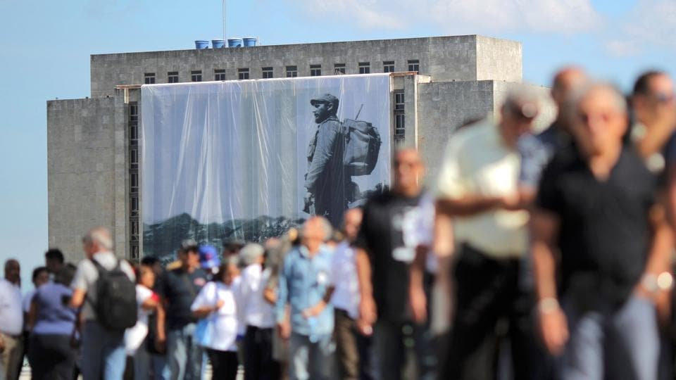 A large portrait of Cuba's late President Fidel Castro hangs from a building while people wait in line to pay tribute to Castro in Havana, Cuba, November 28, 2016.