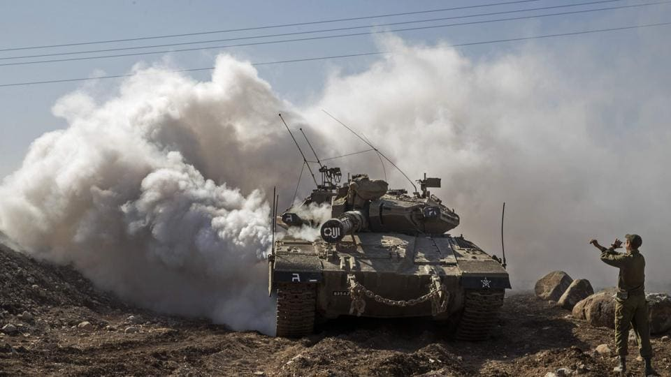 An Israeli soldier directs a Merkava tank near the border with Syria in the Israeli-annexed Golan Heights, on November 28, 2016. Israel's air force targeted gunman linked to the Islamic State group in Syria overnight, the army said, after they fired on an Israeli soldier in the occupied Golan Heights. (AFP)