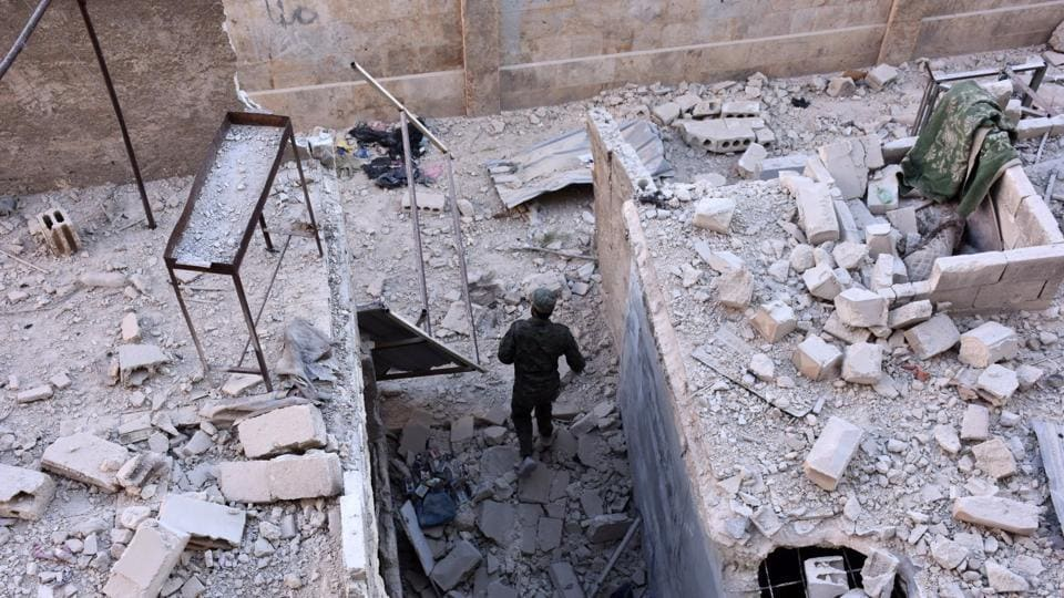 A member of Syrian pro-government forces inspects an area on November 27, 2016 in the Masaken Hanano district in eastern Aleppo, a day after they resized it from rebel fighters. Syria regime forces seized two new rebel-held districts in Aleppo a day after they retook the largest opposition-controlled neighbourhood in the second city, a monitor said. The capture of Masaken Hanano -- which had been the biggest rebel-held district of Aleppo -- was a major breakthrough in a 13-day regime offensive to retake the entire city. / AFP PHOTO / GEORGE OURFALIAN (AFP)